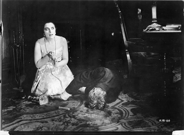 Géraldine Farrar jouant Marcia Manot apeurée est à genoux aux cotés de Tully Marschall, dans le rôle de Silas Martin, gisant sur le sol du bureau dans 'The Devil Stone' de Cecil B. DeMille