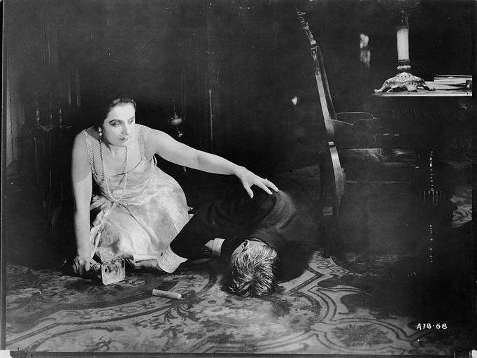 Dans un bureau, Géraldine Farrar jouant Marcia Manot à genoux touche d'une main l'épaule de Tully Marschall, dans le rôle de Silas Martin, qui gît au sol et de l'autre tient un bougeoir dans 'The Devil Stone' de Cecil B. DeMille