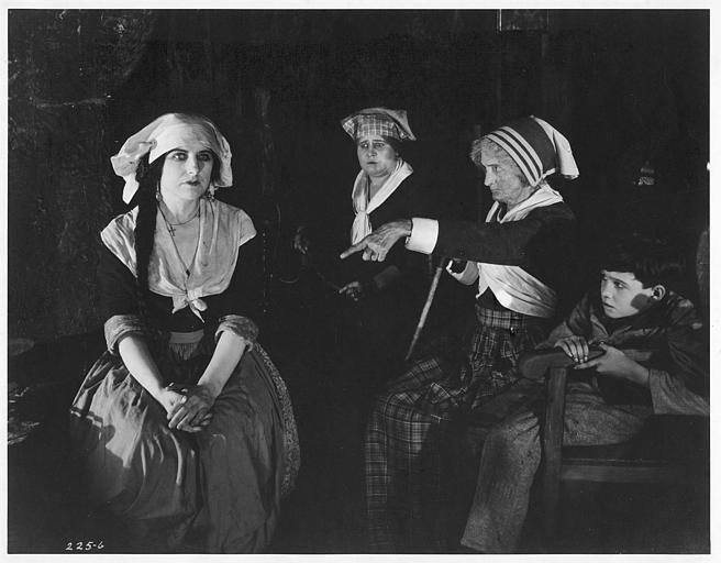 Géraldine Farrar dans le rôle de Marcia Manot est désignée par une autre femme portant une coiffe en présence d'une troisième et d'un enfant dans 'The Devil Stone' de Cecil B. DeMille