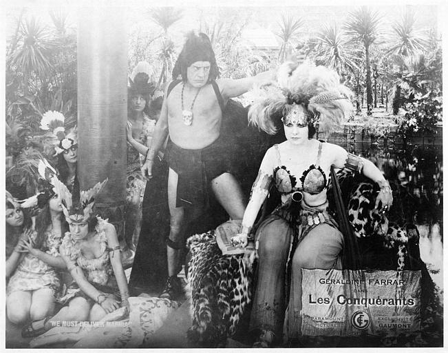 Personnages portant des coiffes à plumes autour de Géraldine Farrar dans le rôle de Tecza trônant dans 'Les Conquérants' (Paramount Pictures)
