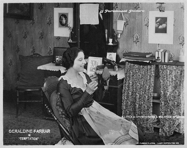 Géraldine Farrar dans le rôle de Renée Duprée cirant une chaussure en souriant dans 'Temptation' de Cecil B. DeMille (Paramount Picture)