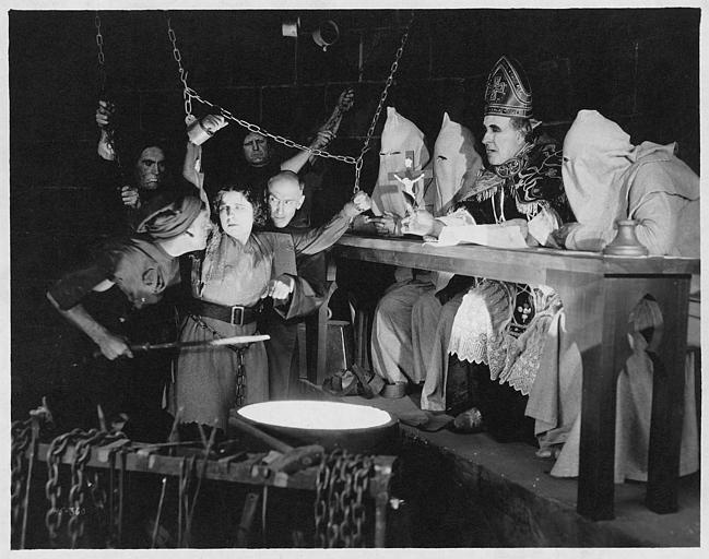 Géraldine Farrar dans le rôle de Jeanne d'Arc est torturée devant un homme d'église et trois hommes masqués dans 'Jeanne d'Arc' de Cecil B. DeMille (Great Photoplay Production)