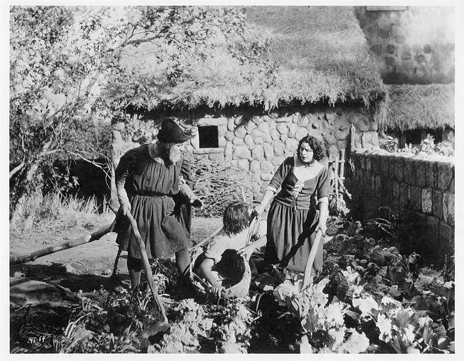Géraldine Farrar dans le rôle de Jeanne d'Arc est dans un potager en compagnie de deux hommes dans 'Jeanne d'Arc' de Cecil B. DeMille