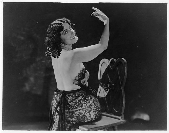 Géraldine Farrar dans le rôle de Concha Perez est assise, en tenue de flamenco, le dos nu et souriante dans 'la femme et le pantin' de Reginald Barker (Goldwyn)