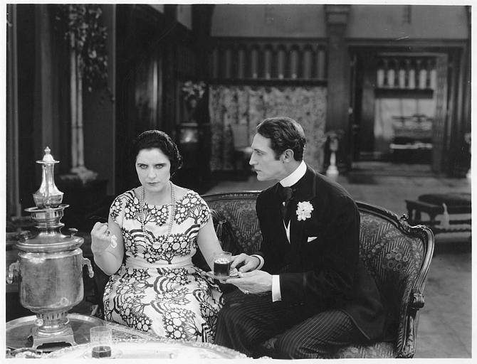 Géraldine Farrar, dans le rôle de Concha Perez au côté de Lou Tellegen qui interprète Don Mateo, tous deux buvant le thé, assis sur un canapé dans 'la femme et le pantin' de Reginald Barker (Goldwyn)