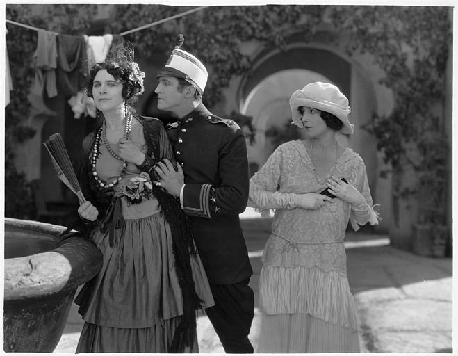 Dans une rue, un homme s'approche d'une femme portant un éventail alors qu'une autre femme les regarde : Géraldine Farrar est Concha Perez et Lou Tellegen est Don Mateo dans 'la femme et le pantin' de Reginald Barker (Goldwyn)