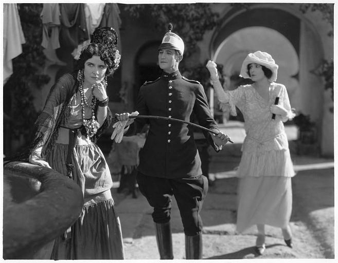 Dans une rue, une femme s'appuyant sur un bassin, avec un homme pliant une cravache et une femme derrière eux levant le poing : Géraldine Farrar est Concha Perez et Lou Tellegen est Don Mateo dans 'la femme et le pantin' de Reginald Barker (Goldwyn)