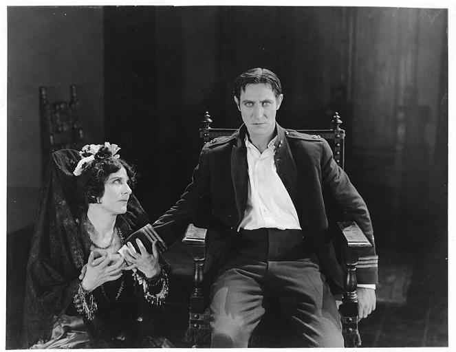 Géraldine Farrar dans le rôle de Concha Perez, en tenue traditionnelle espagnole, pleure en étant assise plus bas que Lou Tellegen qui interprète Don Mateo dans 'la femme et le pantin' de Reginald Barker (Goldwyn)