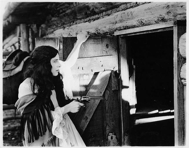 Géraldine Farrar interprétant Concha Perez avec ses cheveux longs lâchés pointe un revolver dans l'ouverture d'une porte dans 'la femme et le pantin' de Reginald Barker (Goldwyn)
