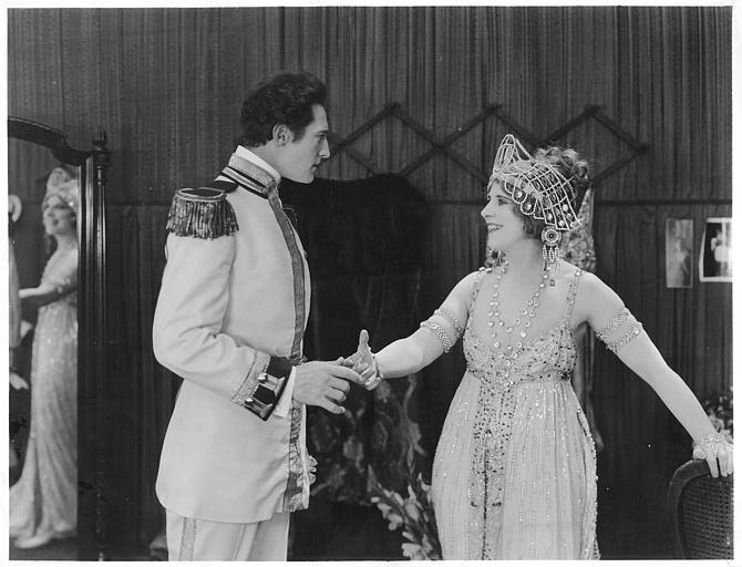 Géraldine Farrar portant un costume de spectacle avec des strass et des perles serrant la main à un officier