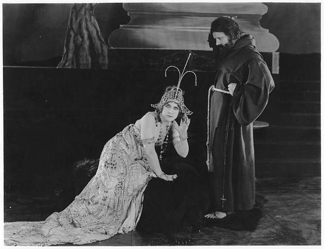 Géraldine Farrar portant un costume de spectacle avec des strass mimant l'écoute aux pieds d'un religieux