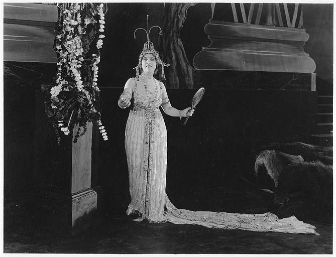 Géraldine Farrar vêtue d'un costume de spectacle avec des strass portant un miroir et jouant une scène