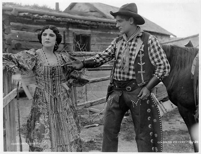Géraldine Farrar dans le rôle de Pancha O'Brien et Milton Sills dans celui du Sheriff Jack Webb discutant à l'entrée d'un enclos où se trouve un cheval dans 'The hell cat' de Willard Mack (Goldwyn Pictures)