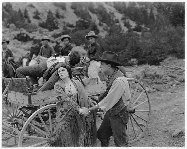Géraldine Farrar dans le rôle de Pancha O'Brien et Milton Sills dans celui du Sheriff Jack Webb se prenant par les mains derrière un chariot qui transporte un homme qui a un couteau dans la poitrine dans 'The hell cat' de Willard Mack (Goldwyn Pictures)