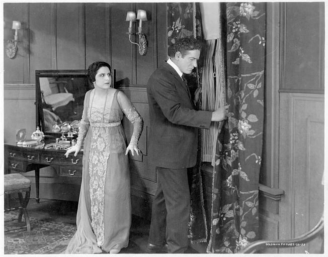 Géraldine Farrar est aux côtés d'un homme qui espionne à la fenêtre derrière un rideau dans 'Shadows' de Willard Mack (Goldwyn Pictures)