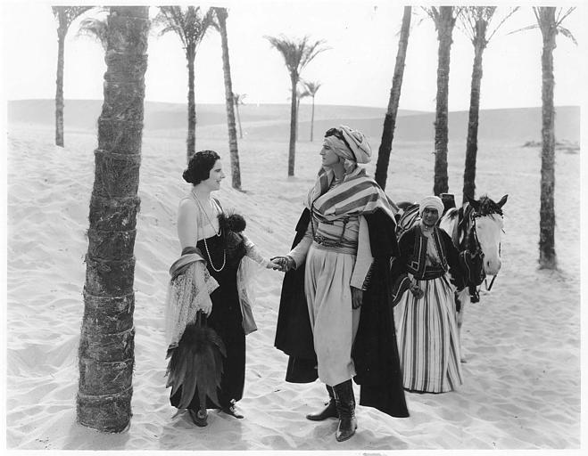 Géraldine Farrar serre la main à un homme qui porte un turban dans le désert