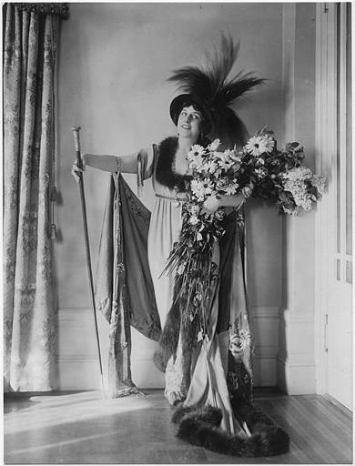 Portrait de Géraldine Farrar portant un chapeau à plume, un bouquet de fleurs et une canne
