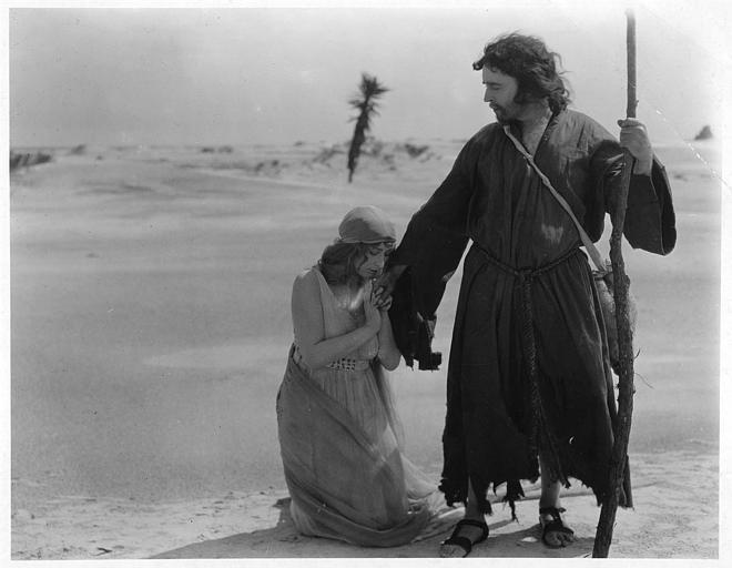 Dans le désert, Thaïs, interprétée par Mary Garden supplie Paphnutius, interprété par Hamilton Revelle, dans 'Thais' de Hugo Ballin et Franck Crane Hall (Goldwyn Pictures)