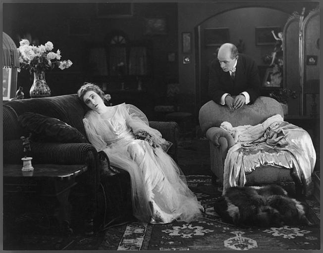 Dans un salon, Saova Gallone est assise dans un fauteuil et Alex Bernard s'accoude sur un autre dans 'Visages de l'amour' de Carmine Gallone