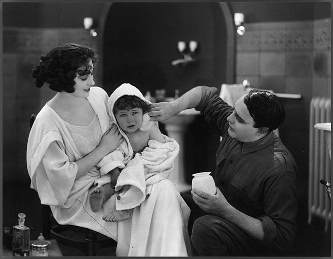 Saova Gallone portant un bébé sur ses genoux avec un homme accroupi à leurs côtés