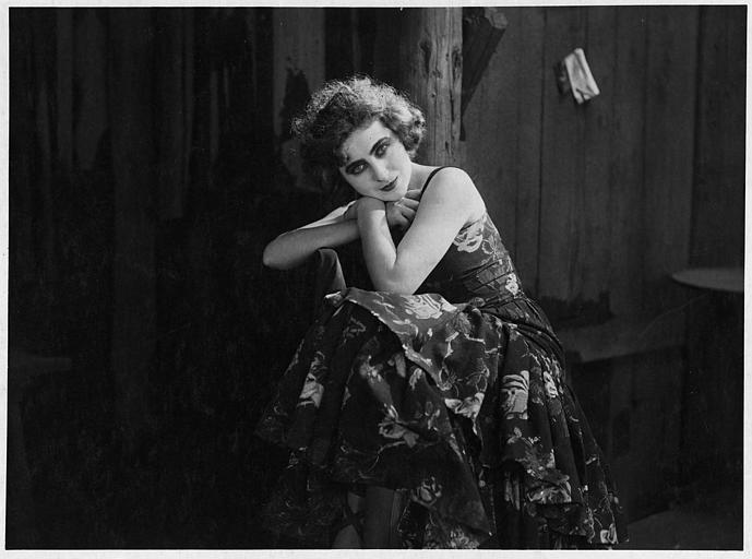Saova Gallone portant une robe fleurie, assise sur une chaise