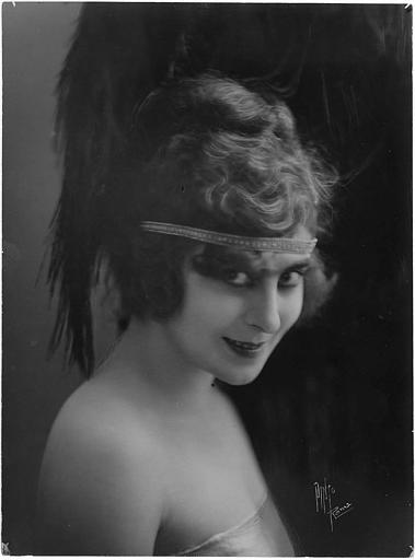 Portrait de Saova Gallone souriante avec une coiffe en plume