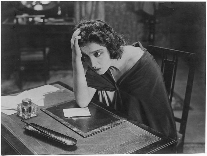 Maria Jacobini le coude sur un bureau, la tête appuyée contre sa main dans 'Il Viaggio' de Gennaro Righelli