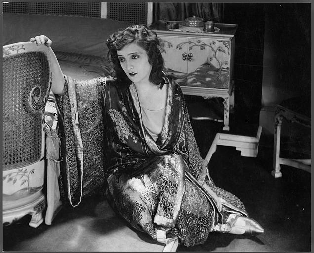Maria Jacobini assise sur le sol  à côté d'un fauteuil
