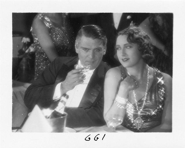 Un homme et Diana Karenne dans le rôle de Mme Beauchêne buvant du champagne durant une soirée dans 'Fécondité' de Nicolas Evreinoff et Henri Étiévant