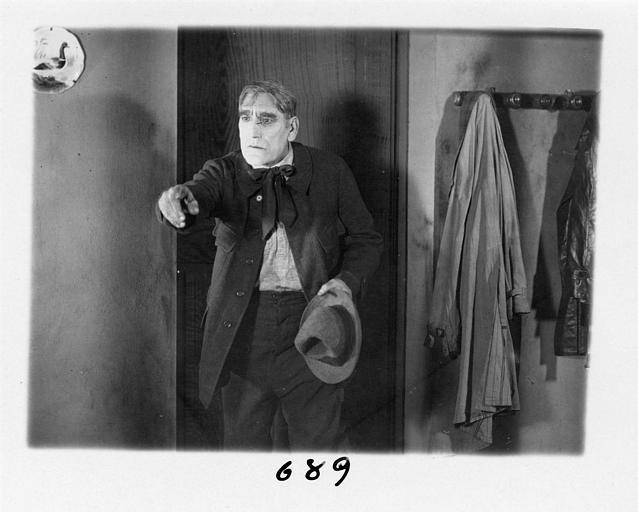 Un homme près d'une porte pointant son doigt vers l'avant dans 'Fécondité' de Nicolas Evreinoff et Henri Étiévant