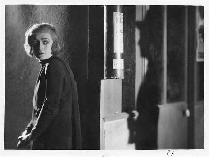 Diana Karenne dans le rôle de Mme Beauchêne est suivie par l'ombre d'un homme portant un chapeau dans 'Fécondité' de Nicolas Evreinoff et Henri Étiévant