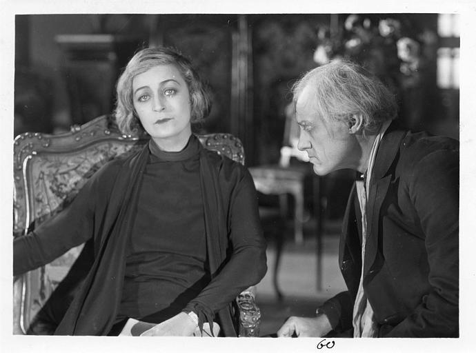 Diana Karenne dans le rôle de Mme Beauchêne est assise dans un fauteuil et discute avec Alexandre Mihalesco dans 'Fécondité' de Nicolas Evreinoff et Henri Étiévant