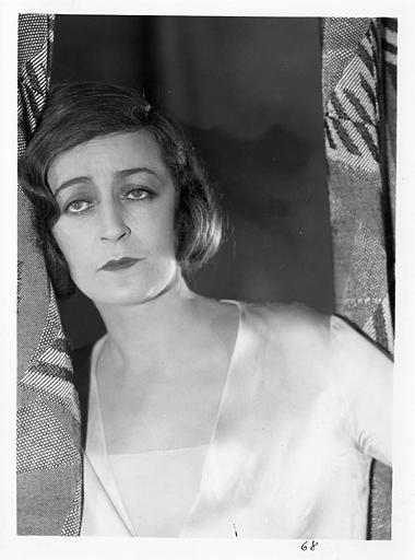 Diana Karenne dans le rôle de Mme Beauchêne se tient à un rideau dans 'Fécondité' de Nicolas Evreinoff et Henri Étiévant