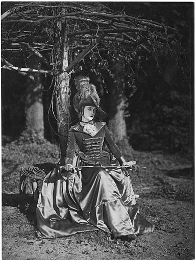 Diana Karenne assise sur un banc de fortune, une cravache à la main