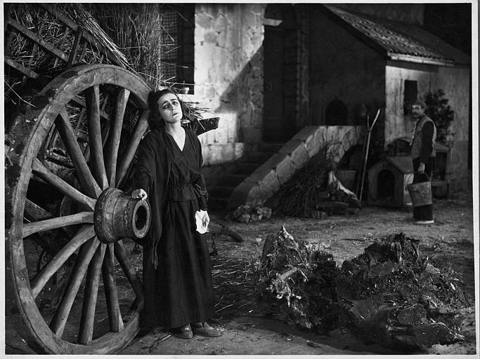 Diana Karenne appuyée contre une roue de charrette avec à l'arrière plan un homme portant des seaux d'eau