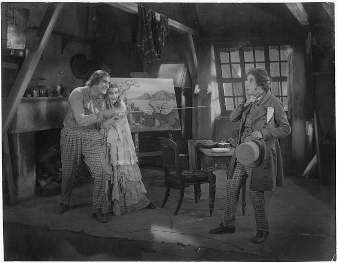Un homme et une femme souriant en train d'étrangler un troisième homme à l'aide d'une longue corde : Elena Lunda, Julius Brandt et Wilhelm Dierterle dans 'Bohème' de Gennaro Righelli