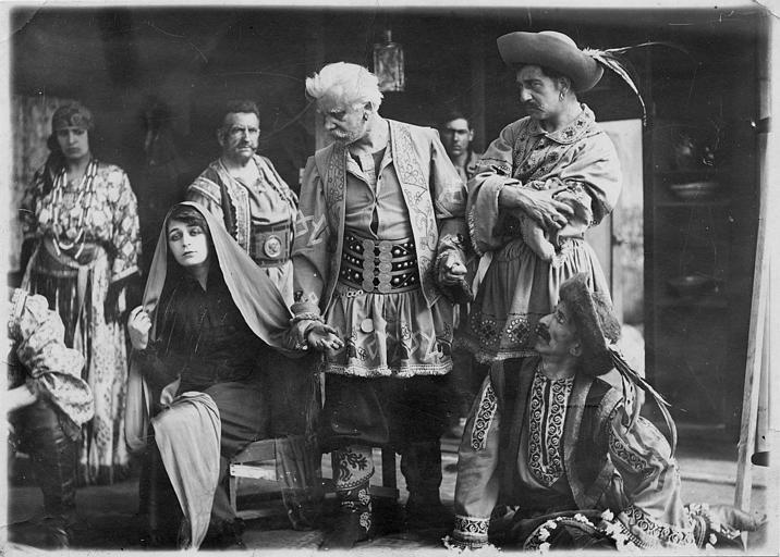 Diana Karenne, un foulard sur la tête, est assise entourée de plusieurs hommes en costume
