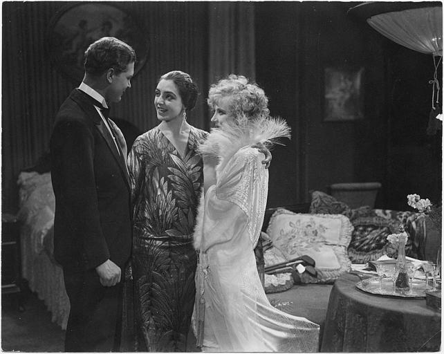 Deux femmes et un homme discutant debout dans un salon : Carmen Boni dans le rôle d'Angelica et Gustav Fröhlich dans celui de Fürst dans 'Gehetzte Frauen' de Richard Oswald