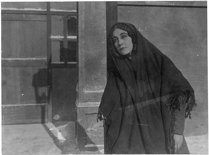 Leda Gys en noir avec un foulard sur la tête dans une rue