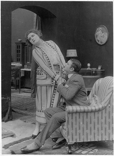Un homme assis dans un fauteuil attirant une femme debout