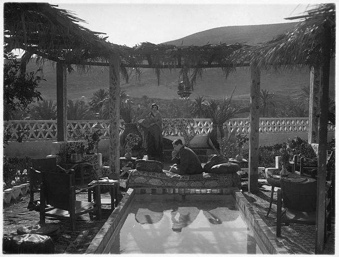 Un homme sur un sofa au bord d'un bassin réfléchit tandis qu'il est observé par Maria Jacobini qui joue le rôle de la Baronne Irène de Rysbergue dans 'Maman Colibri' de Julien Duvivier
