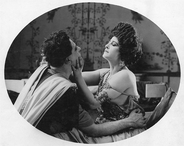 Une femme tenant dans ses mains le visage d'un homme qui lui fait face, tous deux étant habillés de costumes inspirés de l'Antiquité