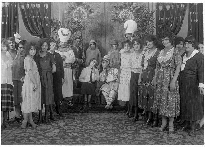 Rémond Frau interprète Dandy, assis au côté d'une femme, la capitaine des girls, entourés de deux rangées d'acteurs de chaque côté : Georgette Rémond, Max l'eunuque et Louis dans 'Dandy-Pacha' de Georges Rémond