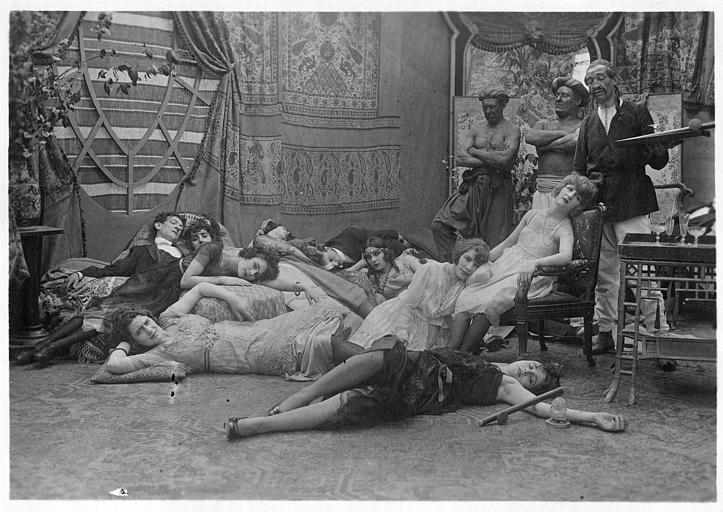Des femmes au sol fumant de l'opium et trois eunuques les surveillant : Broquin, Max l'eunuque et Footitt dans 'Dandy-Pacha' de Georges Rémond