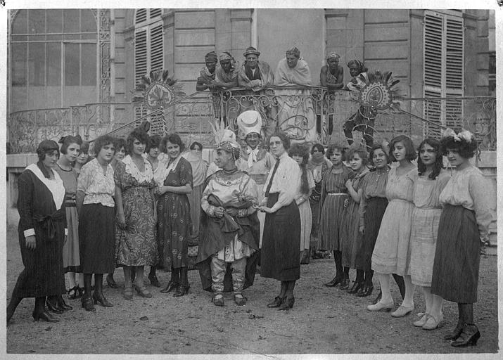 Rémond Frau qui interprète Dandy et la capitaine des girls sont entourés de femmes devant l'entrée d'une demeure dans 'Dandy-Pacha' de Georges Rémond