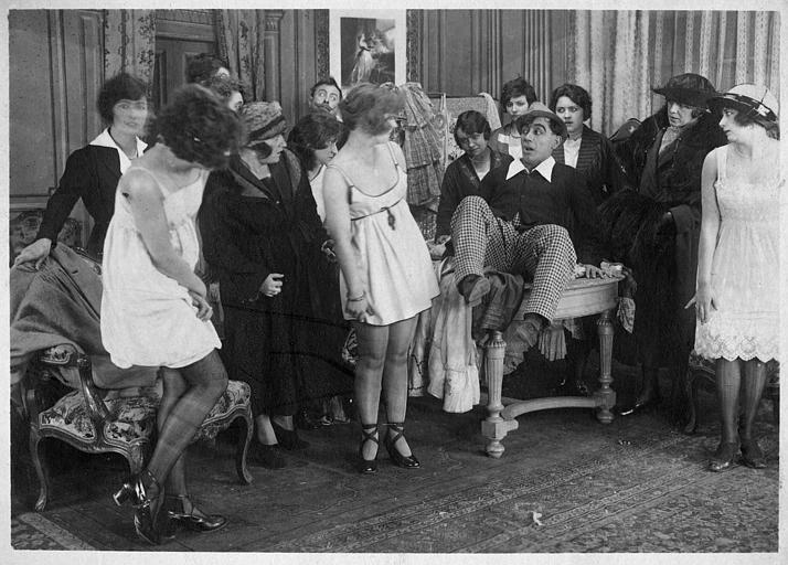Rémond Frau qui interprète Dandy sur une table au milieu de femmes dont Madame Ulysse, Germaine Cottin, Minie et Easton Ulysse dans 'Dandy-Pacha' de Georges Rémond