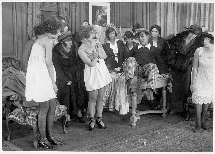 Rémond Frau qui interprète Dandy souriant sur une table au milieu de femmes dont  Madame Ulysse, Germaine Cottin, Minie et Easton Ulysse dans 'Dandy-Pacha' de Georges Rémond