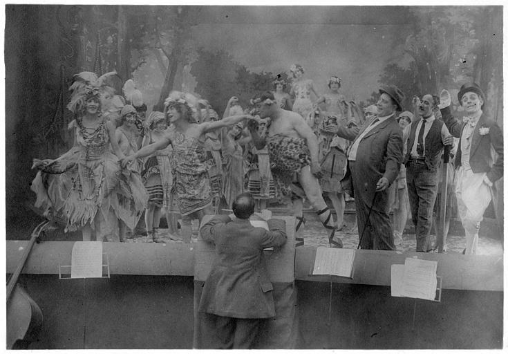 Rémond Frau qui interprète Dandy au milieu de femmes portant des plumes sur une scène de spectacle : Dandy, Easton Ulysse, Smote et Max dans 'Dandy-Pacha' de Georges Rémond