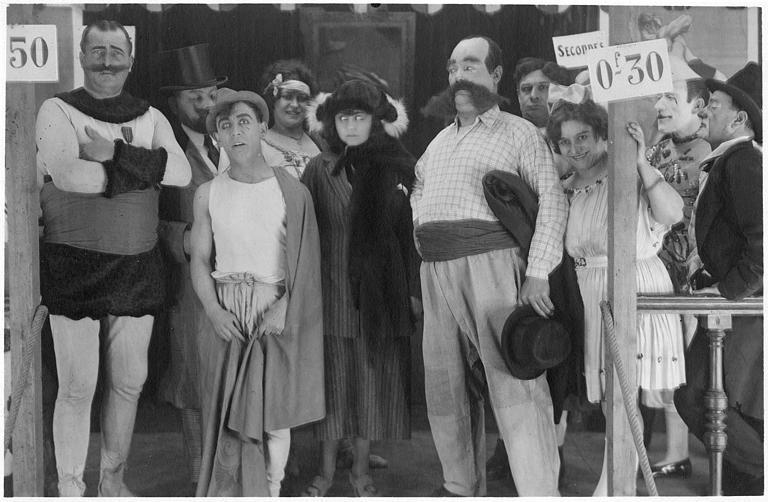 Rémond Frau qui interprète Dandy entouré de personnages de cirque sur une estrade : Florelle, Louis, Adolphe, Dalty, Pollos et Foch dans un épisode de 'Dandy' de Georges Rémond