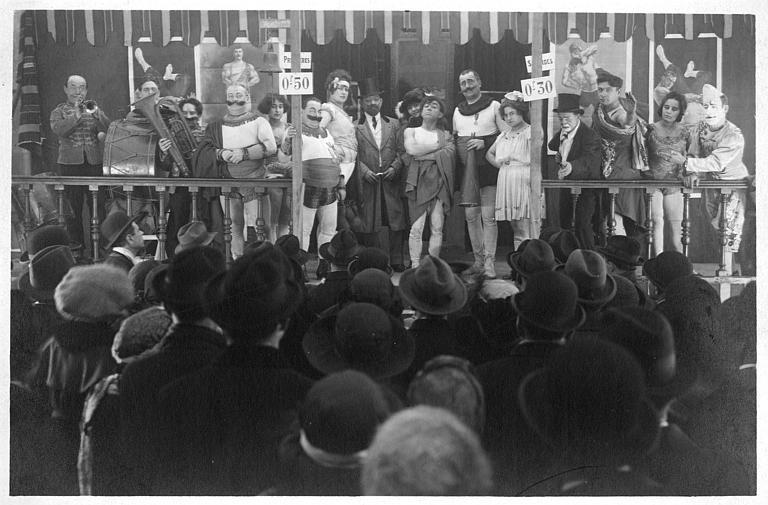 Rémond Frau qui interprète Dandy entouré de personnages de cirque sur une estrade face au public : Dandy, Florelle, Dalty, Pollos, Adolphe, Louis et Foch dans un épisode de 'Dandy' de Georges Rémond